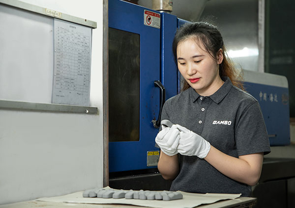 a female worker is checking plastic parts besides an injection machine